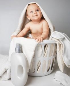 Mosolygó baba ül a szennyeskosárban